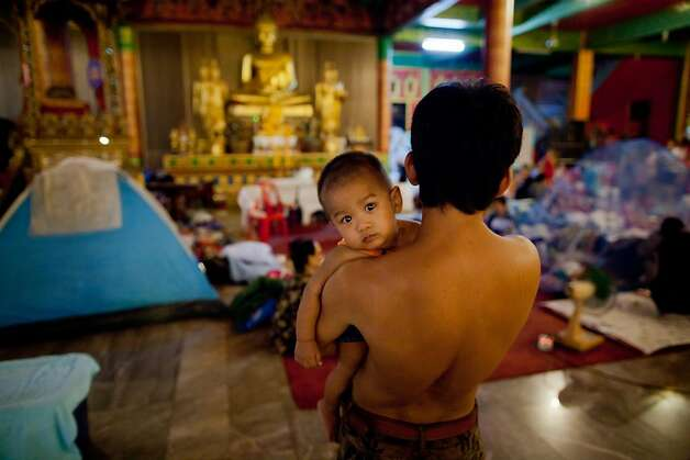 BANGKOK, THAILAND - OCTOBER 31: A baby is held by his father as they and other families settle in for the evening, as they find refuge in a makeshift relief flood centre located at a flooded temple on October 31, 2011 in Bangkok, Thailand.  Around 370 people have died in flood-related incidents since late July according to the Department of Disaster Prevention and Mitigation. Thailand is experiencing the worst flooding in 50 years with damages running as high as USD 6 billion which could increase as the floods swamp Bangkok.  (Photo by Daniel Berehulak /Getty Images) Photo: Daniel Berehulak, Getty Images