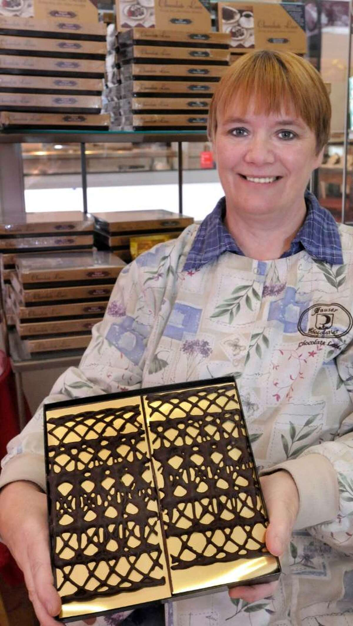 Hauser Chocolatier store manager, Debbie Linnhoff, holds chocolate lace in the Bethel shop on Wednesday, Oct.14,2009.