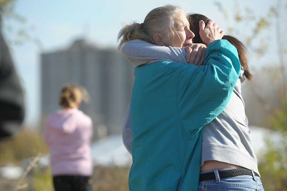Ramona Keil, embraces one of her grandchildren Sunday morning Oct. 30, 2011 in Atchison, Kan. as they wait to hear news of her son Travis Keil, who is missing following a explosion at the Bartlett Grain Company. Three people are confirmed dead and three others missing in the aftermath of a grain elevator explosion in Atchison, Kan., Saturday night. Emergency personnel are now in a recovery operation for the three missing individuals. (AP Photo/St. Joseph News-Press, Todd Weddle) Photo: Todd Weddle, AP