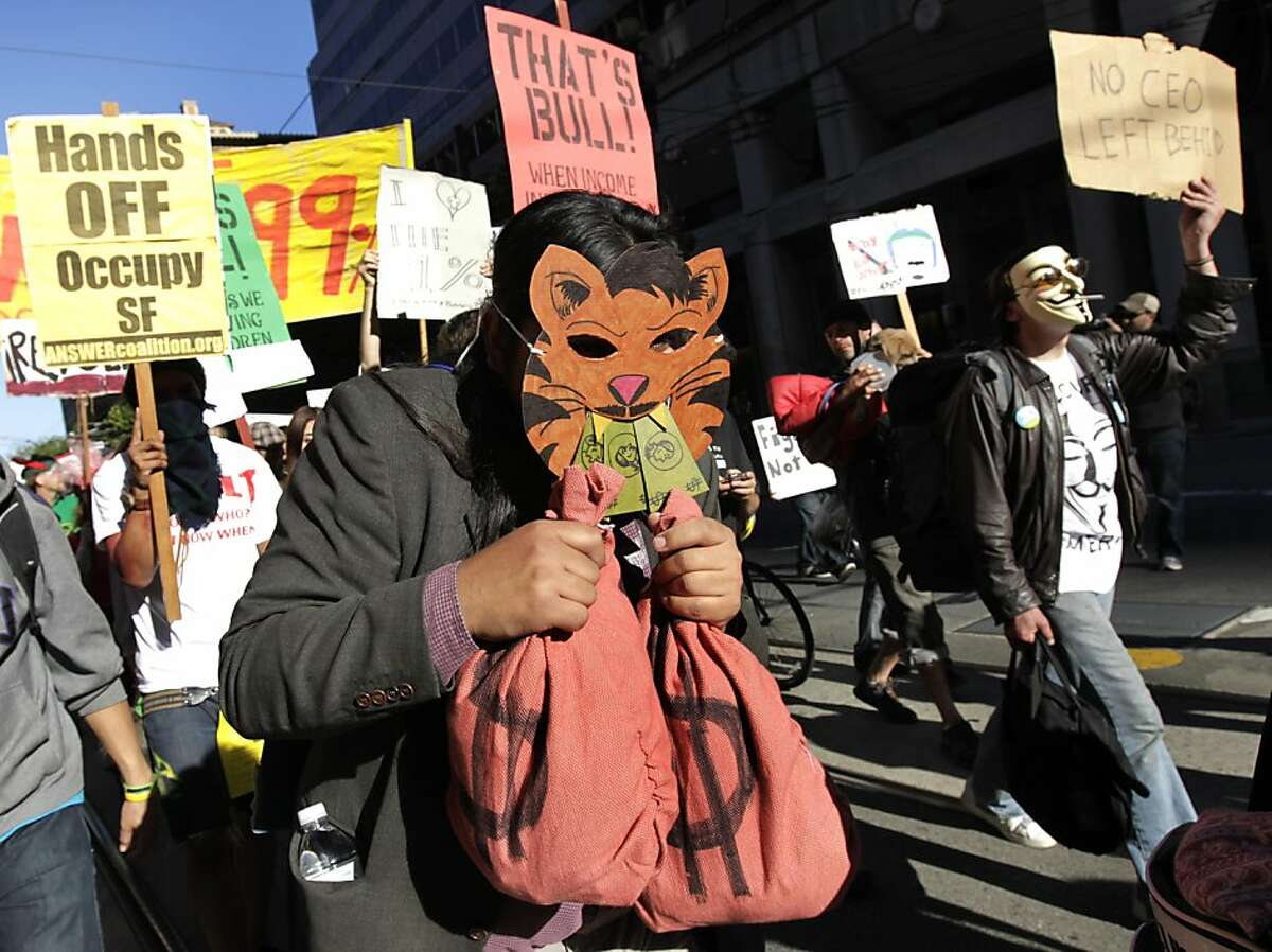 An Occupy SF protester, wearing a fat cat Halloween costume clutching bags of money, marches down Market Street in San Francisco, Calif. on Saturday, Oct. 29, 2011.