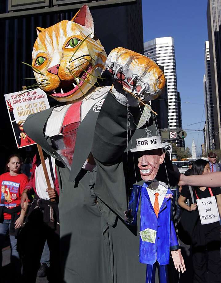 An Occupy SF protester, wearing a fat cat Halloween costume carrying a politician puppet, marches on Market Street in San Francisco, Calif. on Saturday, Oct. 29, 2011. Photo: Paul Chinn, The Chronicle