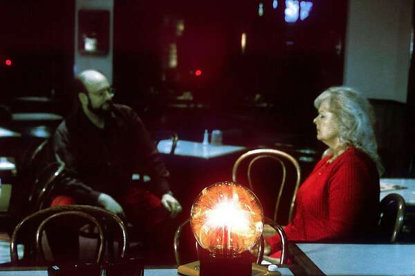 PNGHOST 5/C/05FEB99/PF/LH--Paranormal investigator Lloyd Auerbach (left) asks questions to psychic Annette Martin (right) as she is leading a seance, talking through the Blue Lady at the Moss Beach Distillery.  Photo by Liz Hafalia