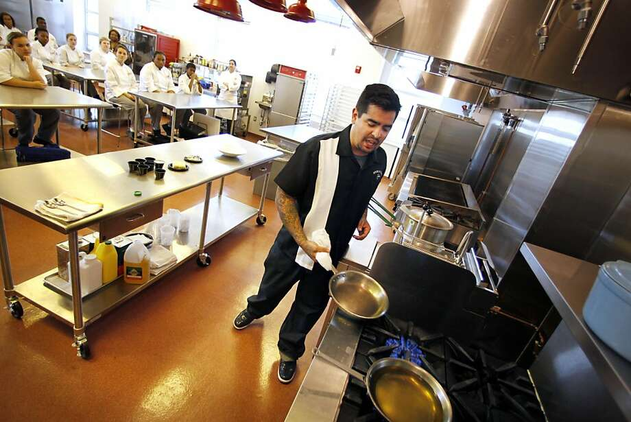 "Celebrity chef Aaron Sanchez, one of the judges on the Food Network's ""Chopped"" and co-star of the show ""Heat Seekers,"" heats oil in pans as he prepares a shrimp and grits recipe during a visit with culinary students at New Orleans Center of Creative Arts in New Orleans, Tuesday, Oct. 25, 2011. (AP Photo/Gerald Herbert) Photo: Gerald Herbert, AP"