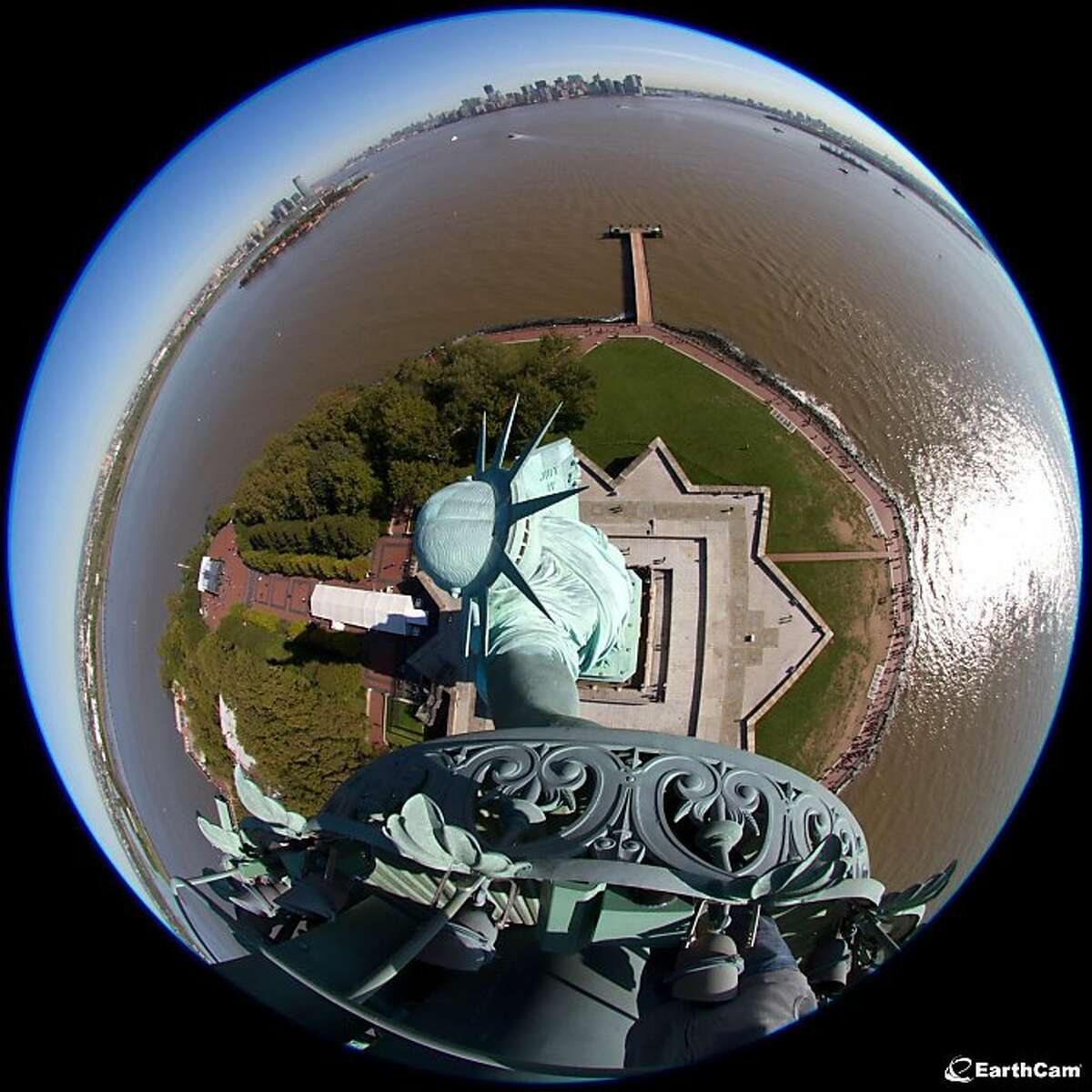 This undated photo provided by EarthCam, shows the Statue of Liberty in New York Harbor, in New York, through a fisheye lens mounted in its torch. Five torch cams will be switched on Friday, Oct. 28, 2011, during a ceremony to commemorate the statues dedication. The five cameras, which will be on 24 hours, 7 days a week, were donated to the National Park Service by Earthcam Inc., a New Jersey-based company that manages a network of webcams around the world. (AP Photo/EarthCam, James Nicoll)