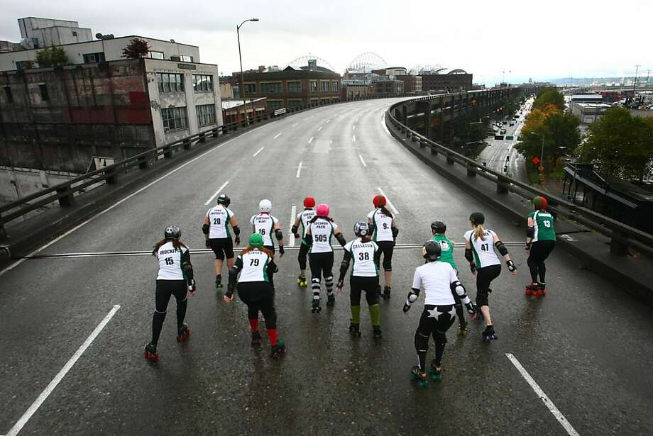 Members of the Rat City Rollergirls flat-track roller derby league skate on the upper deck of the closed Alaskan Way Viaduct on Saturday, October 22, 2011 in downtown Seattle. They were winners of a contest where organizations made pitches about what they would do on the deck of the closed highway for half an hour. The highway usually carries 110,000 cars per day and will be closed for 9 days as demolition of the southern half of the aging structure begins. The highway, built in the 1950's, will be replaced with a new deep bore tunnel along the Seattle waterfront. (AP Photo/seattlepi.com, Joshua Trujillo) Photo: Joshua Trujillo, AP