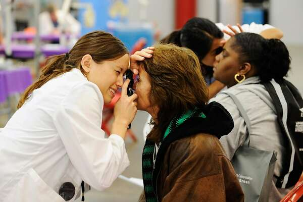 LOS ANGELES, CA - OCTOBER 20:  Women get their eyes checked during during a free health clinic at the Los Angeles Memorial Sports Arena on October 20, 2011 in Los Angeles, California. The clinic operated by CareNow LA, a Los Angeles-based nonprofit group, will serve nearly 5,000 uninsured and underinsured people over next four days. The goal is to serve about 1,200 people each day, providing free medical, dental or vision care by more than 800 medical professionals. Services being offered at the clinic include medical screenings, women's health exams and chiropractors, acupuncturists and other specialists.  (Photo by Kevork Djansezian/Getty Images)