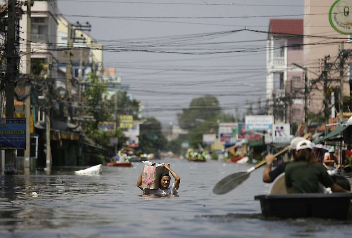 A Thai resident braves chest-deep floods in Rangsit district at the outskirts of Bangkok, Thailand on Friday Oct. 21, 2011. Thailand's Prime Minister Yingluck Shinawatra urged Bangkok's residents to get ready to move their belongings to higher ground Friday as the country's worst floods in half a century began seeping into the capital's outer districts. (AP Photo/Aaron Favila)