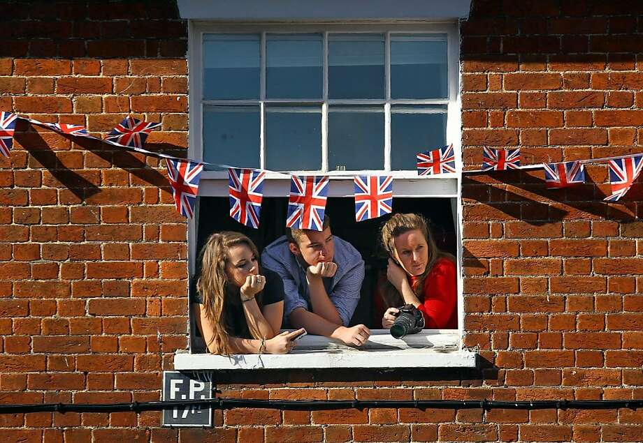 WOOTTON BASSETT, ENGLAND - OCTOBER 16:  People watch from a window during a ceremony to celebrate the town gaining the title Royal Wootton Bassett  on October 16, 2011 in Wootton Bassett, England. The town of Wootton Bassett is to be the first in more than 100 years to get the title of Royal in recognition of its efforts to honour the UK's war dead due to the repatriations of fallen troops passing through the town since 2007.  (Photo by Matt Cardy/Getty Images)  Ran on: 10-17-2011 Residents of Wootton Bassett, England, have a lofty view of the royal event. Photo: Matt Cardy, Getty Images