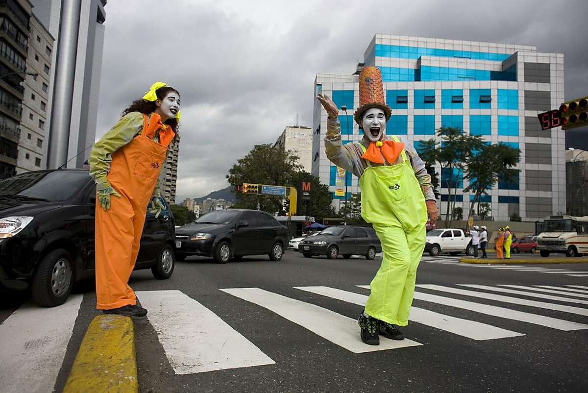 Mimes gesture as they stand in a crosswalk in Caracas, Venezuela, Friday Oct. 7, 2011. The mayor of the city's eastern district of Sucre has launched a unique program aimed to encourage civility among reckless drivers and careless pedestrians, putting 120 mimes at intersections to politely and silently scold violators. The campaign kicked off this week as mimes posted at busy intersections mocked people who jaywalked or acted brutish behind the wheel. (AP Photo/Ariana Cubillos) Ran on: 10-16-2011 Mimes gesture in a crosswalk in Caracas to encourage civility among drivers and pedestrians.