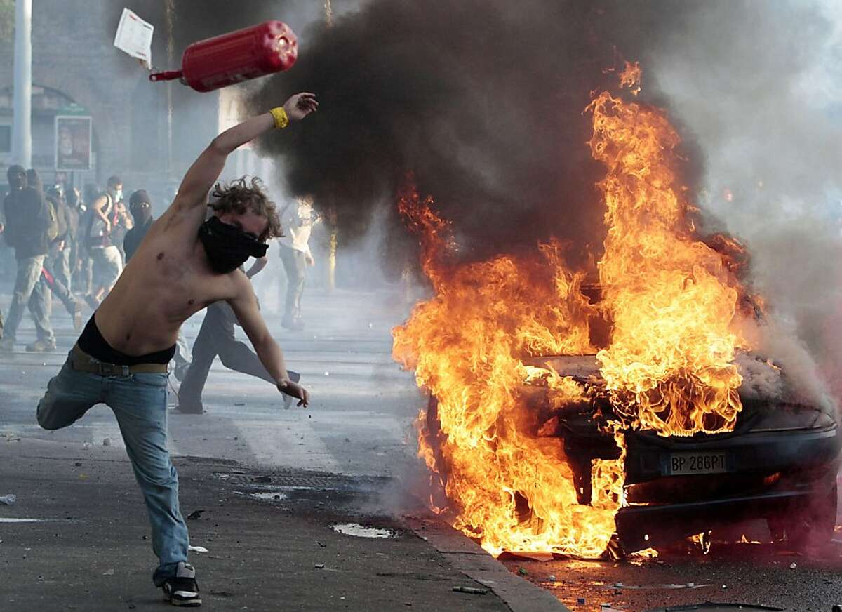 RETRANSMISSION FOR ALTERNATIVE CROP - A protestor hurls a cannister clashes in Rome, Saturday, Oct. 15, 2011. Protesters smashed the windows of shops in Rome and torched a car as violence broke out during a demonstration in the Italian capital, part of worlwide protests against corporate greed and austerity measures. (AP Photo/Gregorio Borgia) Ran on: 10-16-2011 A man hurls a canister at a burning car as violent demonstrators smashed windows and torched vehicles after breaking away from a peaceful protest of corporate greed. Ran on: 10-16-2011 A man hurls a canister at a burning car as violent demonstrators smashed windows and torched vehicles after breaking away from a peaceful protest of corporate greed.