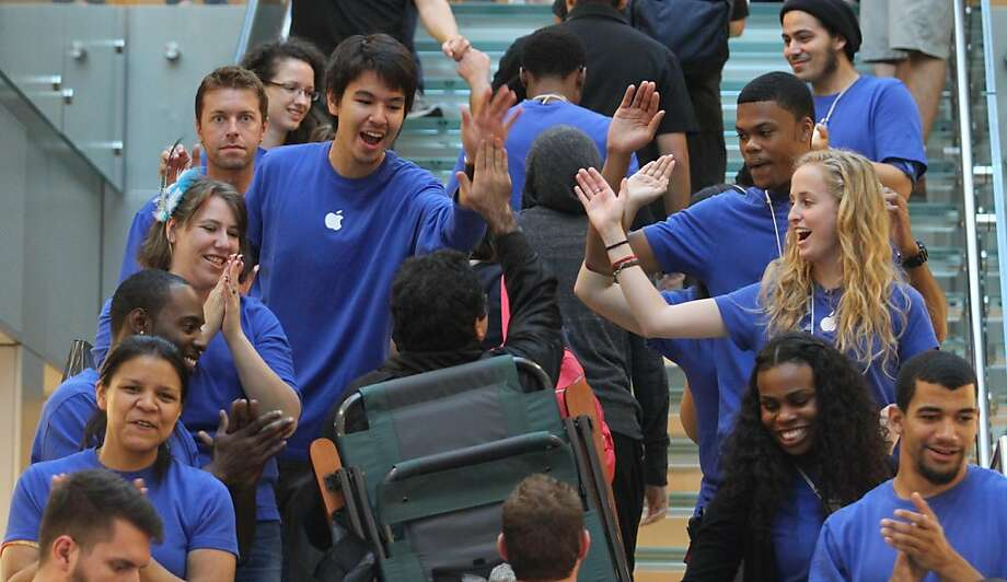 Apple employees welcome a customer to the Stockton St. store as the company releases its new iPhone 4S. Photo: Mathew Sumner, Special To The Chronicle