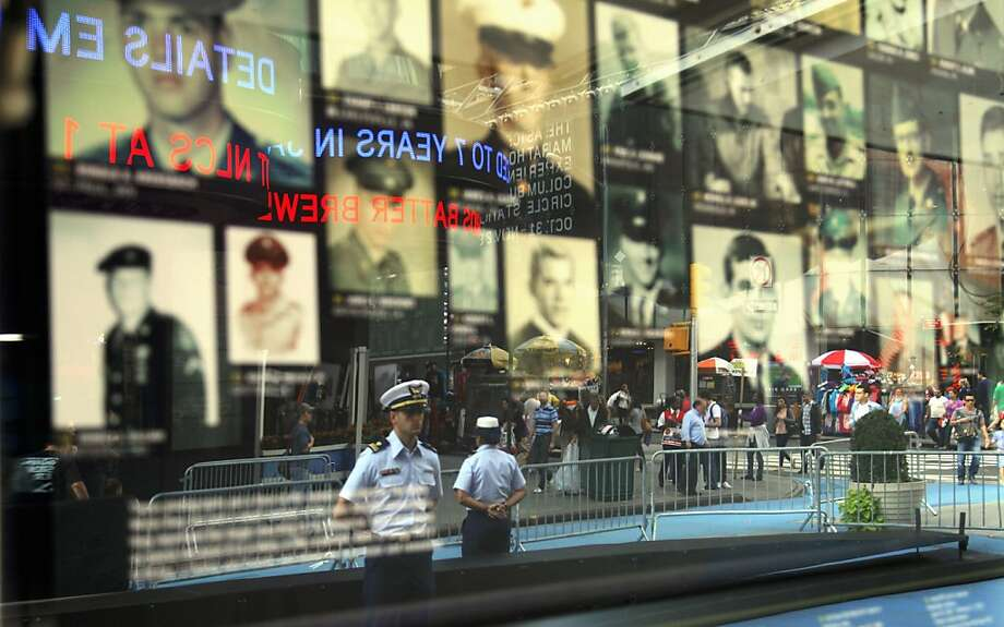 "Photographs of military personnel killed in action in Vietnam are on display in New York's Times Square during a kick off ceremony of the Vietnam Veterans Memorial Fund (VVMF) nationwide ""Call for Photos"" Tuesday, Oct. 11, 2011. The A&E History channel and VVMF launched the initiative, which includes a traveling half-scale replica of the Vietnam Memorial in Washington, D.C., to gather photographs and stories of the 58,272 men and women listed on the Memorial. (AP Photo/Bebeto Matthews) Photo: Bebeto Matthews, AP"