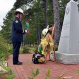 Mississippi State Fire Academy Honor Guard member Rob Fisher sets a flower at the memorial Tuesday, Oct. 11, 2011, during the Mississippi Fallen Firefighter Memorial Service at the academy in Pearl, Miss. (AP Photo/The Clarion-Ledger, Rick Guy)
