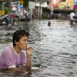 AYUTTHAYA,THAILAND - OCTOBER 10: A Thai man smokes a cigarette as he sits in the flooded streets October 10, 2011 in Ayutthaya, Thailand. Around 200 factories closed in the central Thai province of Ayutthaya because of flooding, which is posing a threat to Bangkok as well. Over 260 people have died in flood-related incidents since late July according to the Department of Disaster Prevention and Mitigation. Some areas of the country are experiencing the worst flooding in 50 years, mainly in the centre, north and northeast. (Photo by Paula Bronstein /Getty Images)