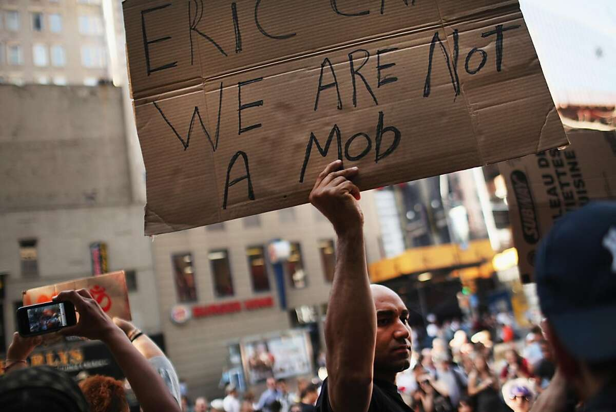 NEW YORK, NY - OCTOBER 10: A Wall Street protester holds up a sign at Zuccotti Park where hundreds of other activists are living on October 10, 2011 in New York City. Hundreds of activists affiliated with the 'Occupy Wall Street' demonstrations have been living in the park in the Financial District near Wall Street. The activists have been gradually converging on the financial district over the past three weeks to rally against the influence of corporate money in politics among a host of other issues. The protests have begun to attract the attention of major unions and religious groups as the movement continues to grow in influence. (Photo by Spencer Platt/Getty Images)