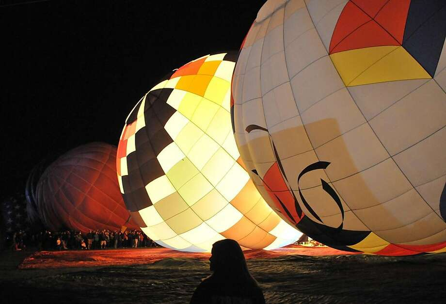 The dawn patrol balloons light up as they are inflated before sunrise at the Albuquerque International Balloon Fiesta on Saturday, Oct. 1, 2011. (AP Photo/Albuquerque Journal, Greg Sober) Photo: Greg Sorber, AP
