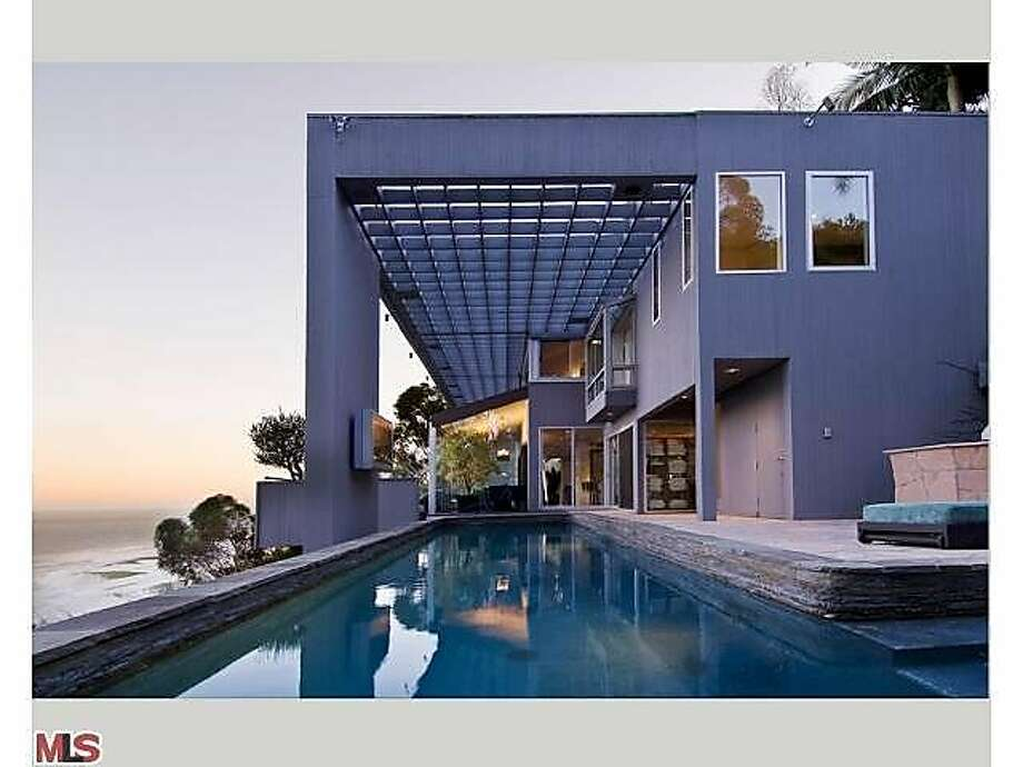 An exterior shot of the home, spotlighting the architecture as well as the pool. Photo: Partners Trust - Beverly Hills