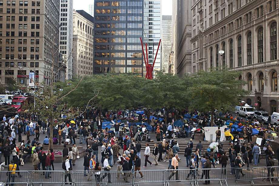 "People and protestors participating in ""Occupy Wall Street"" walk around Zuccotti Park in New York, on Friday, October 7, 2011. The three-week-old campout in a lower Manhattan plaza looks like a jumble of tattered sleeping bags, but teams of volunteers working on food, sanitation, health care and other needs keep the shifting population of protesters functioning like an impromptu city within the city. (AP Photo/Andrew Burton) Photo: Andrew Burton, AP"
