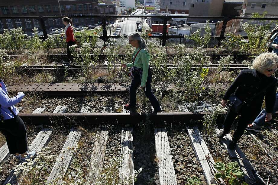 In this Oct. 6, 2011 photo, Sarah McEneaney, center, walks along train tracks on a Reading Railroad Viaduct no longer in use in Philadelphia. A decade-long quest to redevelop a downtown viaduct is getting some traction thanks in part to the success of New York's popular High Line. A community group is extolling the virtues of developing, not demolishing as some would prefer, the Reading Viaduct just north of downtown. (AP Photo/Alex Brandon) Photo: Alex Brandon, AP