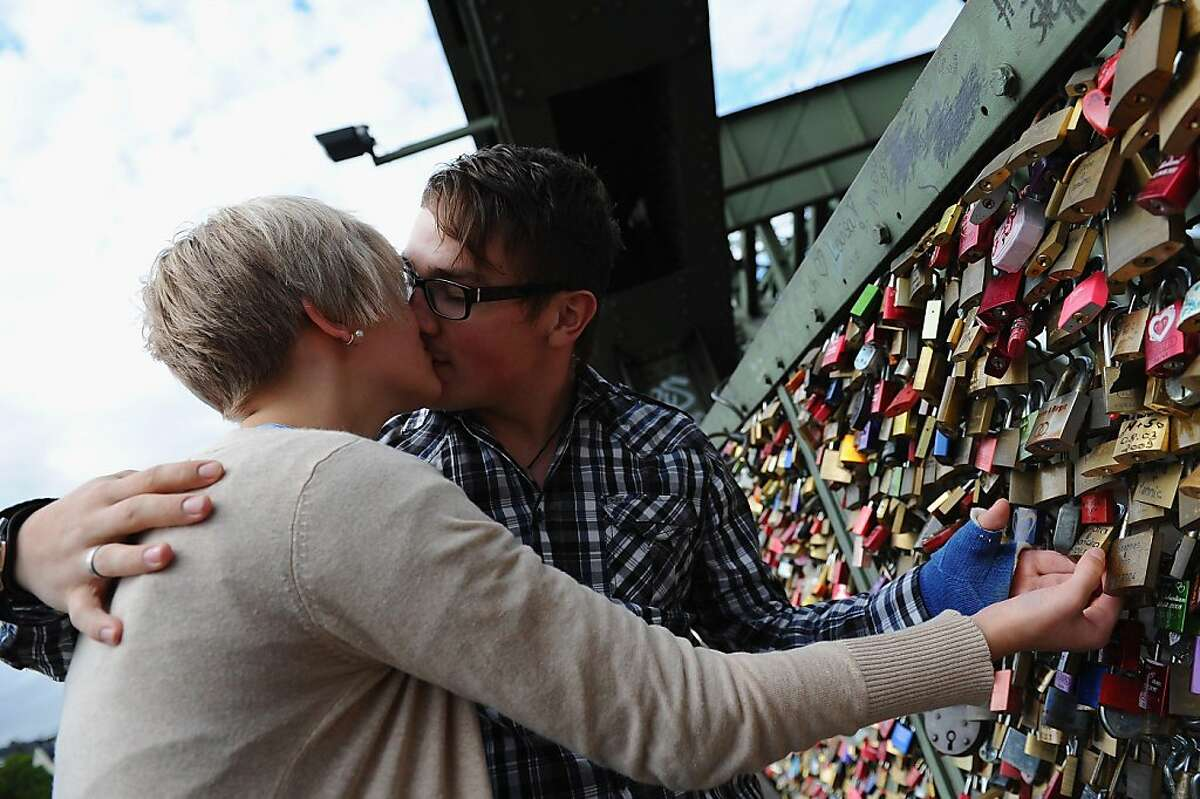 """COLOGNE, GERMANY - SEPTEMBER 13: A young couple kisses next to their personal love lock locked on some time ago. Thousands of so-called """"love locks,"""" or """"love padlocks,"""" hang from a fence across the Hohenzollernbruecke bridge on September 13, 2011 in Cologne, Germany. Love locks are a growing phenomenon in cities across Europe and are meant by the couples who leave them behind as a symbol of their powerful and undying love for one another. (Photo by Dennis Grombkowski/Getty Images)"""