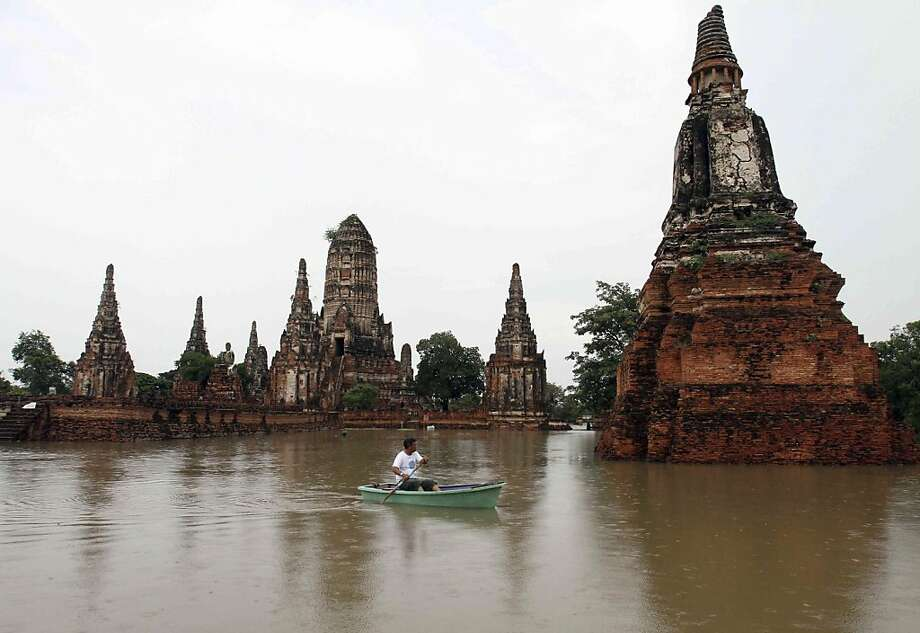 A man rows his boat past Chaiwattanaram temple which was hit by flood in Ayuttaha province, central Thailand Tuesday, Oct. 4, 2011. The Thai government said heavy floods in the country have killed at lease 206 people since August. (AP Photo) Ran on: 10-06-2011 A lone rower passes flooded Chaiwattanaram temple in central Thailand. The worst flooding in half a century has damaged nearly 10 percent of the nation's rice farms and killed 237 people. Photo: Str, AP