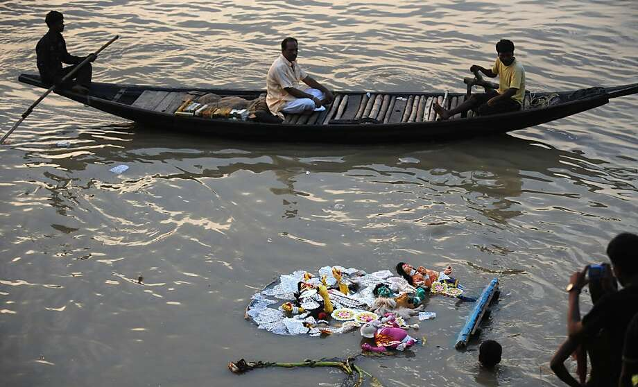 An idol of Hindu goddess Durga floats in the river Ganga after immersion as a boat passes, during the Vijaya Dashami or Dusshera Festival in Kolkata on October 6, 2011, on the final day of Durga Puja. Durga Puja, the annual Hindu festival that involves worship of the goddess Durga who symbolizes power and the triumph of good over evil in Hindu mythology, culminates in the immersion of idols in bodies of water.  AFP PHOTO/Dibyangshu SARKAR (Photo credit should read DIBYANGSHU SARKAR/AFP/Getty Images) Photo: Dibyangshu Sarkar, AFP/Getty Images