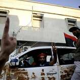 """Libyan rebels flash victory signs as they patrol a street in the capital Tripoli on August 22, 2011. Libyan rebels declared the """"Kadhafi era"""" over after taking control of most of Tripoli, as jubilant fighters streamed into the capital to join battles near the strongman's compound. AFP PHOTO / FILIPPO MONTEFORTE (Photo credit should read FILIPPO MONTEFORTE/AFP/Getty Images)"""