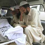 People sit next to their family member killed in target killing in Karachi, Pakistan on Monday, Aug 22, 2011. A senior government official says gunmen have killed four people in Pakistan's largest city, taking the death toll in Karachi to 18 in two days. (AP Photo / Shakil Adil)