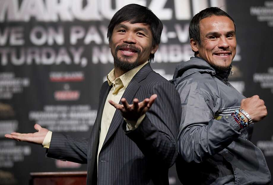 Manny Pacquiao, left, jokes with members of the media while posing for photos with Juan Manuel Marquez during a news conference Wednesday, Nov. 9, 2011, in Las Vegas. Pacquiao and Marquez are scheduled to meet for boxing's WBO welterweight title on Saturday. (AP Photo/Julie Jacobson)  Ran on: 11-12-2011 Manny Pacquiao (left) has four knockdowns in two bouts with Juan Manuel Marquez, who  says he really won both fights. Photo: Julie Jacobson, AP