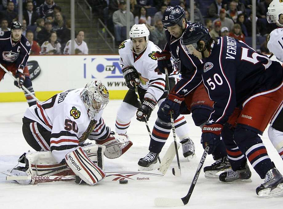 From left to right, Chicago Blackhawks' Corey Crawford makes a save as teammate Niklas Hjalmarsson, of Sweden, Columbus Blue Jackets' RJ Umberger and Antoine Vermette wait for a rebound during the second period of an NHL hockey game on Thursday, Nov. 10, 2011, in Columbus, Ohio. (AP Photo/Jay LaPrete)  Ran on: 11-11-2011 Corey Crawford makes a save as Niklas Hjalmarsson, R.J. Umberger and Antoine Vermette wait to pounce. Photo: Jay LaPrete, AP