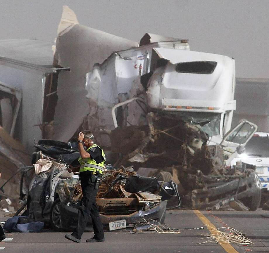 An Arizona Department of Public Safety Officer walks in front of two vehicles that were involved in two crashes that involved 16 vehicles on Interstate 10 near Picacho Peak, about midway between Phoenix and Tucson, Tuesday, Oct. 4, 2011. (AP Photo/Darryl Webb) Photo: Darryl Webb, AP