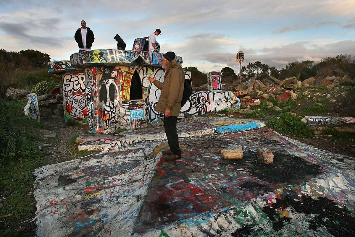 """Longtime Albany Bulb advocate and artist Osha Neumann tours one of the art sculptures known as the """"Castle"""" in Albany, Calif., on Feb. 5, 2009."""