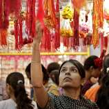 An Indian woman looks at a rakhi, a sacred thread tied on the wrist, at a shop ahead of Raksha Bandhan festival in Ahmadabad, India, Wednesday, Aug. 10, 2011. Raksha Bandhan, the Hindu festival that celebrates the bond between a brother and sister, falls on Aug. 13. (AP Photo/Ajit Solanki)