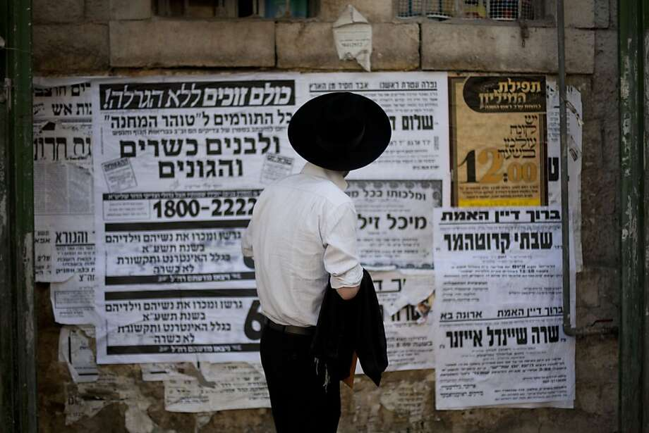 In this photo taken Tuesday, Sept. 27, 2011 An ultra-Orthodox Jewish man reads pashkevilim, posters used to publicize news and important messages in the ultra-Orthodox community, in Jerusalem's religious Mea Shearim neighborhood. An ultra-Orthodox collector has teamed up with Israel's National Library to bring this old-fashioned form of communication into the 21st century by scanning more than 20,000 of the posters into a digital online archive. The project offers a glimpse into one of the main media used by a group trying to hold the line against the march of modernity.(AP Photo/Bernat Armangue) Photo: Bernat Armangue, AP