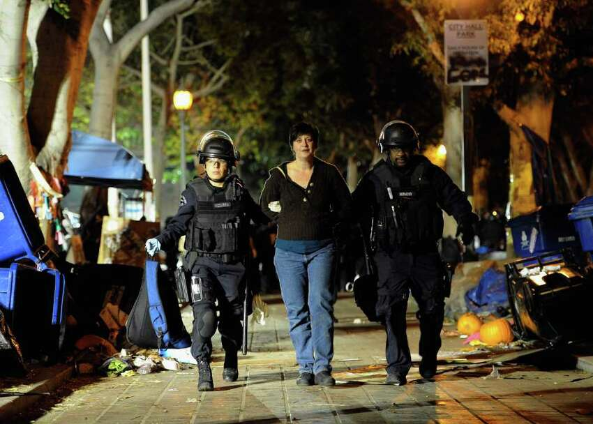 LOS ANGELES, CA - NOVEMBER 30: An Occupy LA protester is led away after getting arrested by Los Angeles Police Department officers who raided their encampment on November 30, 2011 in Los Angeles, California. Protesters have remained on the City Hall lawn despite a deadline, set by Los Angeles Mayor Antonio Villaraigosa, to dismantle their campsite and leave the park which the city declared closed as of 12:01 am November 28th. (Photo by Kevork Djansezian/Getty Images)