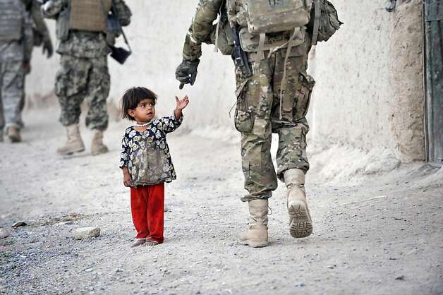 An Afghan girl greets a joint patrol of US troops from the Charlie Company, 2-87 Infantry, 3rd Brigade Combat Team and Afghan National Army soldiers at Kandalay village in the southern Afghan province of Kandahar on August 8, 2011 while US troops launchedmissile attacks on Taliban targets in nearby Kelawai village killing at least three and capturing two insurgents. US forces push their counterinsurgency efforts to battle for the hearts and minds of the local population. Photo: Romeo Gacad, AFP/Getty Images