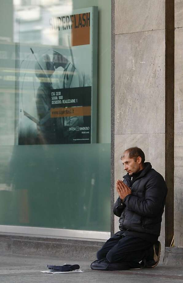 A man begs for money in front of a bank in Milan, Italy, Wednesday, Nov. 9, 2011. Italy's key borrowing rate spiked Wednesday well above the 7 percent level that eventually forced other eurozone countries to seek bailouts, amid uncertainty over who would lead the country when Premier Silvio Berlusconi steps down. (AP Photo/Antonio Calanni) Ran on: 11-10-2011 A man begs for money in front of a bank in Milan, Italy, where the key borrowing rate spiked at 7.4 percent. Photo: Antonio Calanni, AP