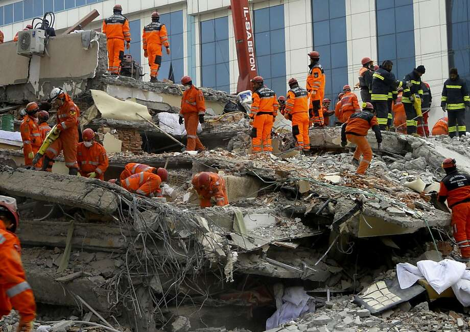 Turkish rescue workers search for survivors in the rubble of a collapsed hotel in Van, Turkey, Friday, Nov. 11, 2011. At least 17 people, including a Japanese aid worker, were killed and dozens of others trapped. The magnitude-5.7 quake was a grim replay of the previous magnitude-7.2 earthquake that hit Oct. 23, killing more than 600 people.(AP Photo/Bertan Ayduk ) Ran on: 11-12-2011 Rescue workers search for survivors in the rubble of a hotel that collapsed in a quake in Van, Turkey. Photo: Bertan Ayduk, AP