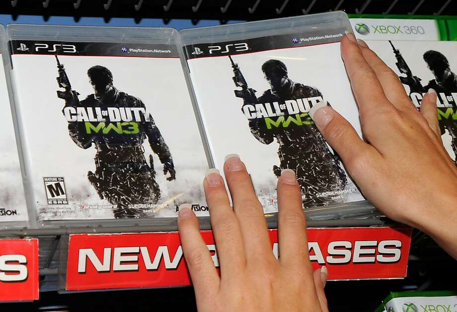 """NORTH LAS VEGAS, NV - NOVEMBER 07:  GameStop employee Randi Taber stacks copies of """"Call of Duty: Modern Warfare 3"""" for the PlayStation 3 during a launch event for the highly anticipated video game at a GameStop Corp. store November 7, 2011 in North Las Vegas, Nevada. Video game publisher Activision released the eighth installment in the '""""Call of Duty"""" franchise at midnight on November 8.  (Photo by Ethan Miller/Getty Images) Photo: Ethan Miller, Getty Images"""