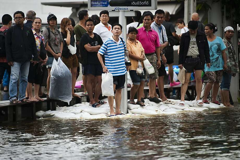 People wait for transportation on an elevated walkway and on sand bags in the flood waters at Mo-Chit BTS (skytrain) station in Bangkok, on November 11, 2011. The Thai capital, built on swampland, is slowly sinking and the floods currently besieging Bangkok could be merely a foretaste of a grim future as climate change makes its impact felt, experts say. AFP PHOTO/ Nicolas ASFOURI (Photo credit should read NICOLAS ASFOURI/AFP/Getty Images) Photo: Nicolas Asfouri, AFP/Getty Images