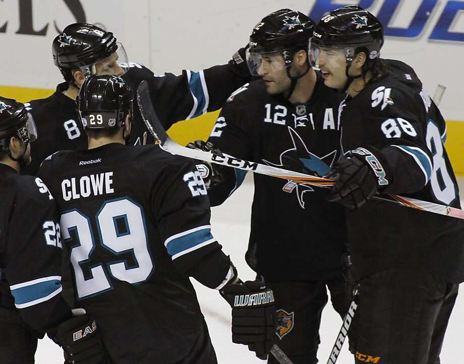 CORRECTS NAME OF PLAYER TO PATRICK MARLEAU - San Jose Sharks' Patrick Marleau, second from right, celebrates with teammates, Ryane Clowe (29), Joe Pavelski, left rear, and Brent Burns after scoring a goal in the in the second period of an NHL hockey game against the Minnesota Wild on Thursday, Nov. 10, 2011, in San Jose, Calif. (AP Photo/George Nikitin)  Ran on: 11-11-2011 Patrick Marleau (12) is congratulated by his Sharks teammates after scoring one of his two goals in the second period. Photo: George Nikitin, AP