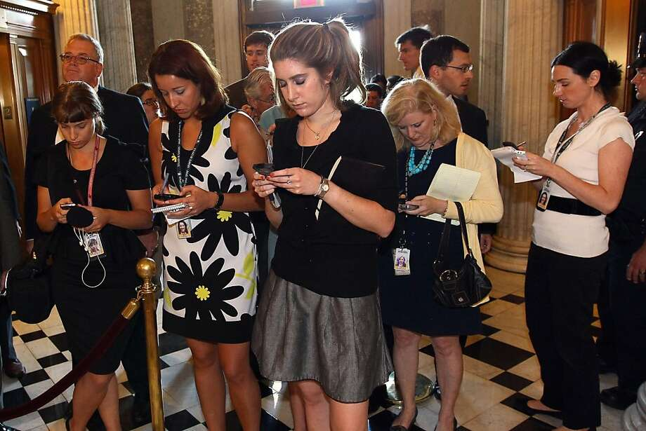 Reporters work on their phones as the U.S. Senate votes on the debt limit bill at the U.S. Capitol on August 2, 2011 in Washington, DC. The Senate voted 74-26 to approve the bill to raise the debt ceiling, allowing the U.S. toavoid default on its debts. Photo: Win McNamee, Getty Images