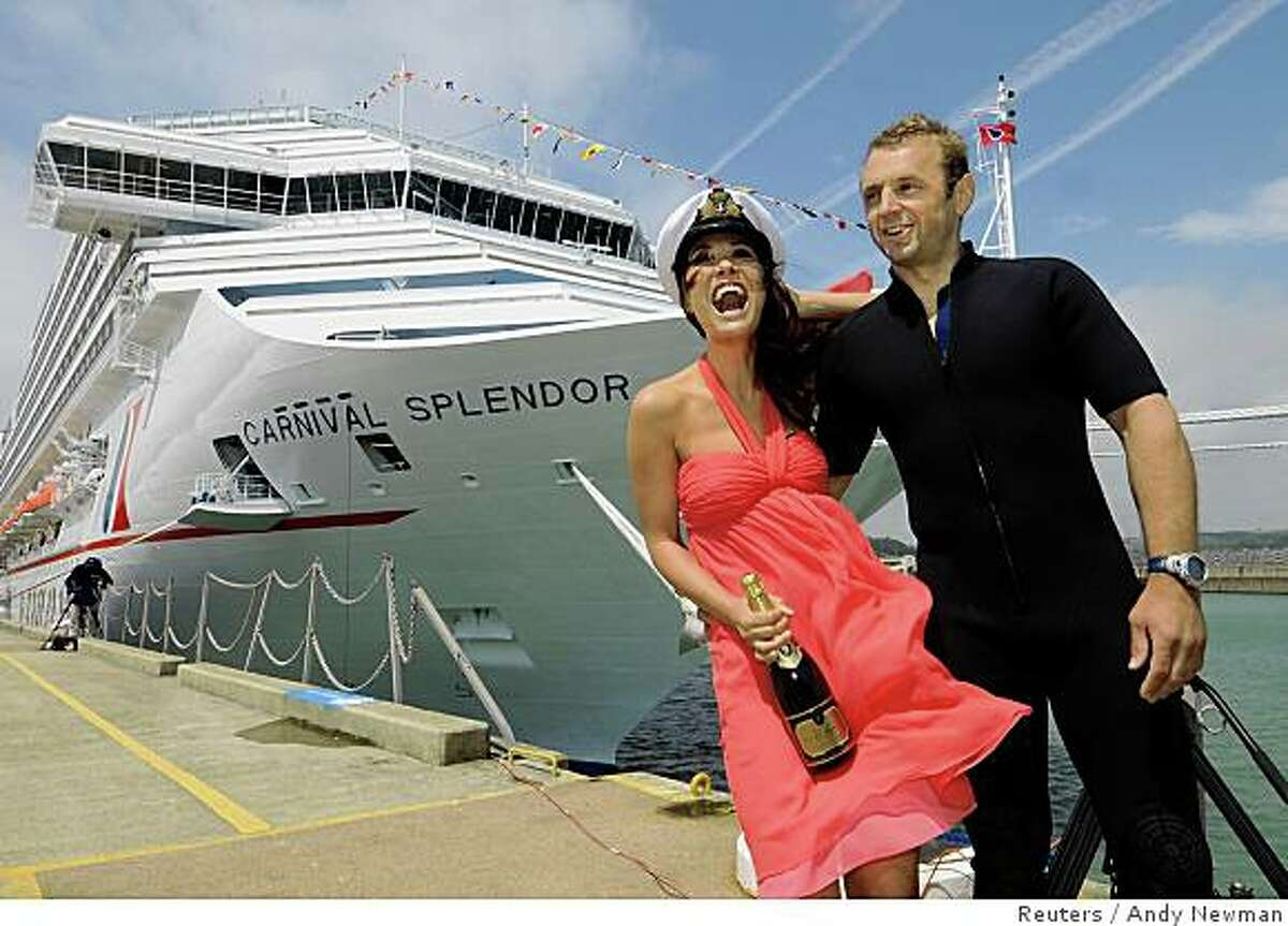 British celebrity Myleene Klass (L) poses with Royal Navy Diver Chris Rumming in front of the new Carnival Splendor in Dover, England, July 10, 2008. The Carnival Splendor, the newest 952-feet-long (290-metre-long) ship of Carnival Cruise Lines' fleet, will begin a series of 12-day Northern Europe cruises on July 13. Klass is present for the ship's formal naming ceremonies. REUTERS/Andy Newman/Carnival Cruise Lines/Handout (BRITAIN). FOR EDITORIAL USE ONLY. NOT FOR SALE FOR MARKETING OR ADVERTISING CAMPAIGNS. NO SALES. NO ARCHIVES.