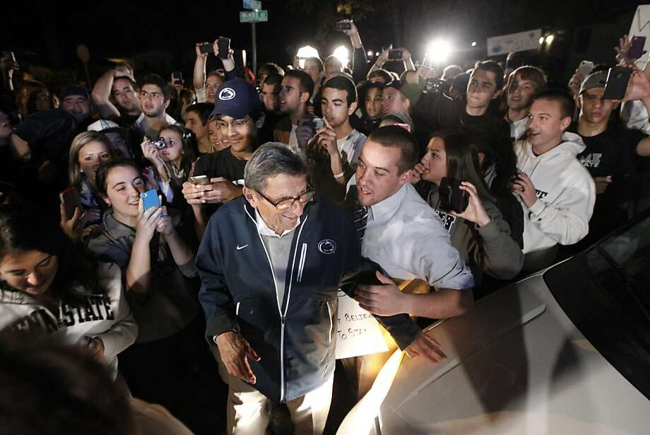 "Students greet Penn State football coach Joe Paterno as he arrives at his home, Tuesday, Nov. 8, 2011, in State College, Pa. Paterno's support among the Penn State board of trustees was described as ""eroding"" Tuesday, threatening to end the 84-year-old coach's career amid a child sex-abuse scandal involving a former assistant and one-time heir apparent. (AP Photo/Matt Rourke) Photo: Matt Rourke, AP"
