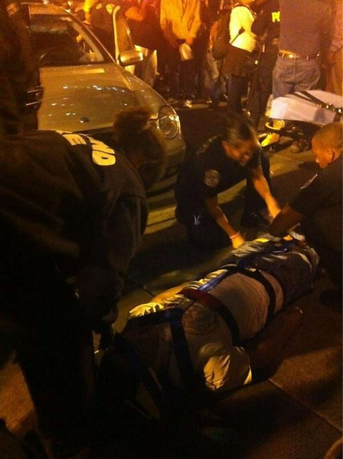 An injured Occupy Oakland protester is treated after being struck by a car at 11th Street and Broadway.