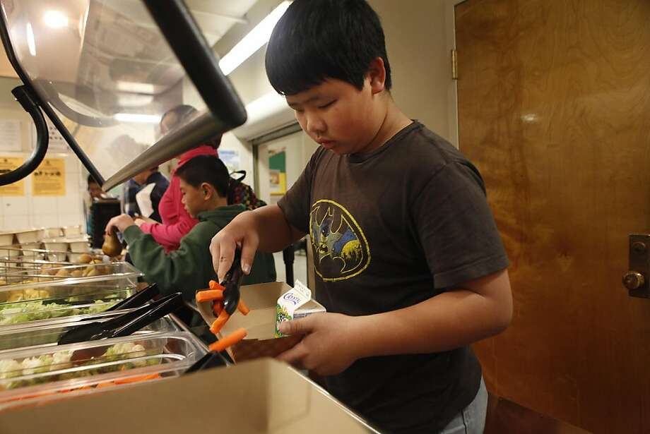 Tony Lei, 12, selects some carrots from the salad bar during lunch in the cafeteria at Francisco Middle School on Tuesday, November 8, 2011 in San Francisco, Calif.  Lunches for the day included chicken nuggets with sweet potatoes, mac and cheese with mixed vegetables, turkey breast and pepper jack cheese on wheat sammie and bean and chicken tamale with rice along with salad bar and selection of fruit. According to a new report from the California Center for Public Health Advocacy, the percentage of overweight or obese children fell 1.1 percent from 2005 to 2010.  Improvements in the San Francisco Unified School District (SFUSD) school meals include the improvement of it's vegetable offering by increasing the amount of dark green and orange vegetables. SFUSD meals which do not contain artificial flavoring or colors and and does not permit trans fats except for naturally occurring fats in beef and cheese, which are not considered a health risk.  There are salad bars at all middle and high schools and elementary schools without salad bars serve a fresh pack of vegetables to its students and include fresh produce and whole grains each day. Photo: Lea Suzuki, The Chronicle