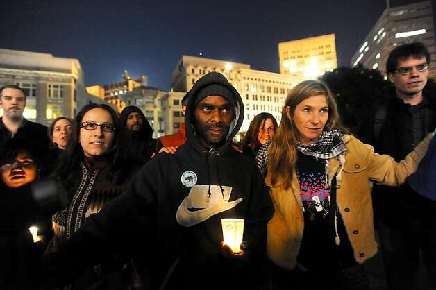 Darron Cotton, center, joins Occupy Oakland protesters in a candlelight vigil for a man gunned down at the edge of the encampment on Thursday, Nov. 10, 2011, in Oakland, Calif. Photo: Noah Berger, Special To The Chronicle