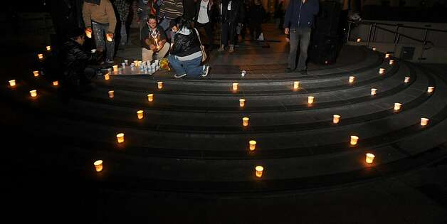 Occupy Oakland protesters lay candles around Frank Ogawa plaza in memory of a man murdered at their camp's edge on Thursday, Nov. 10, 2011, in Oakland, Calif. Photo: Noah Berger, Special To The Chronicle