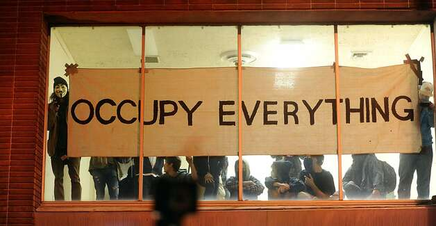 Occupy Oakland protesters claim a vacant building during a march on Wednesday, Nov. 2, 2011, in Oakland, Calif. Thousands of anti-Wall Street protesters took to Oakland's streets as part of a day-long series of events, called a citywide strike, aimed at asserting the movement's strength and shutting down commerce. (AP Photo/Noah Berger) Photo: Noah Berger, AP