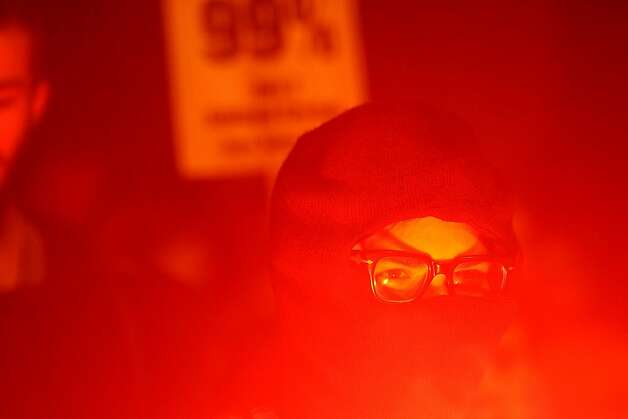 An Occupy Oakland protester, lit by a flare, rallies on Wednesday, Nov. 2, 2011, in Oakland, Calif. Thousands of anti-Wall Street protesters took to Oakland's streets as part of a day-long series of events, called a citywide strike, aimed at asserting the movement's strength and shutting down commerce. (AP Photo/Noah Berger) Photo: Noah Berger, AP